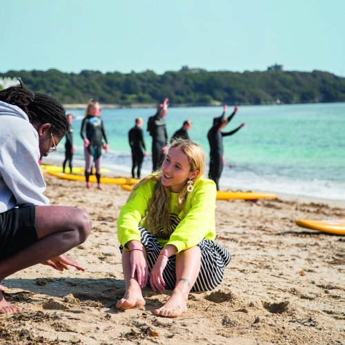 Two students talking on the beach in Falmouth