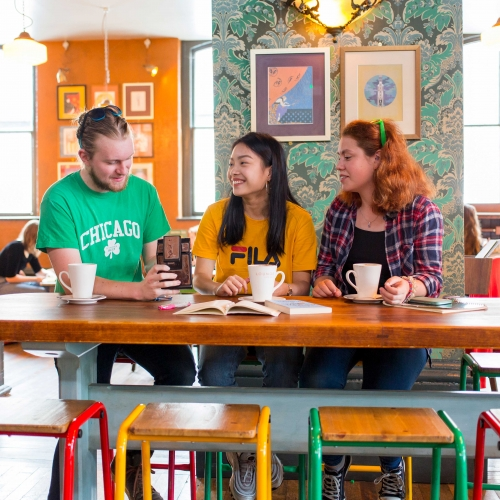 Brightly dressed students having coffee in brightly decorated cafe.