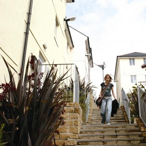 Student walking down steps between buildings.